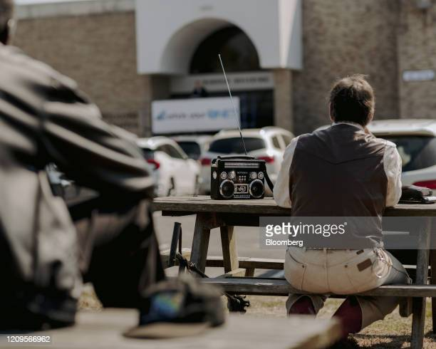 Member of First Baptist Church listens to a sermon on a radio while sitting in the parking lot in West Memphis, Arkansas, U.S., on Sunday, April 5,...