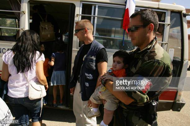 A member of French Commando Hubert holds a baby before boarding him into a bus as he secures an evacuation of foreign nationals from the southern...