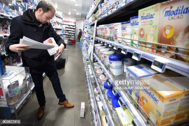 A member of French General Directorate of Competition Policy Consumer Affairs and Fraud Control checks baby milk products in a pharmacy on January 11...