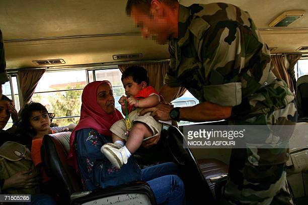 A member of French Hubert commando passes a baby to his mother as the unity secures an evacuation of foreign nationals from the southern town of...
