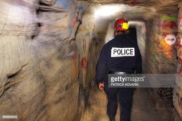 Member of French special police squad 'Brigade d'intervention de la compagnie sportive' walks in a tunnel in the catacombs of Paris on August 20 2009...