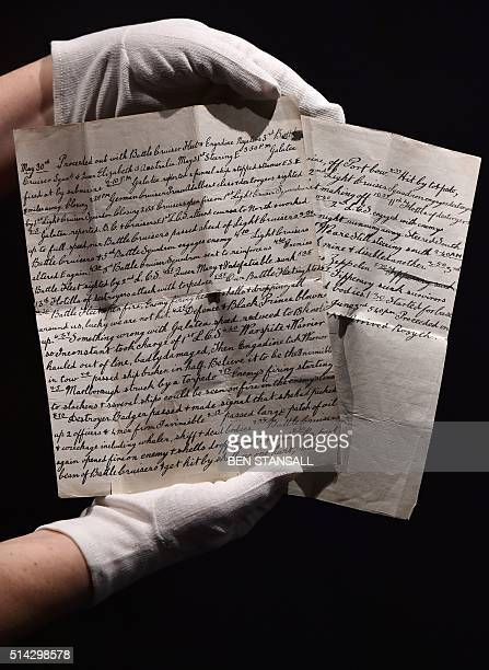 A member of gallery staff holds a letter from sailor William Henry Spowart documenting his time fighting at the battle of Juland as part of World War...