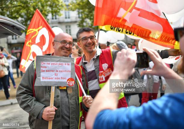 A member of General Confederation of Labour French worker's union holds a sign reading 'You can't at the same time tighten the belt and drop your...