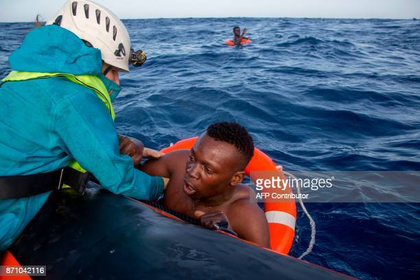 A member of German NGO SeaWatch helps a migrant to board a boat after he was recovered in the Mediterranean Sea on November 6 2017 During a shipwreck...