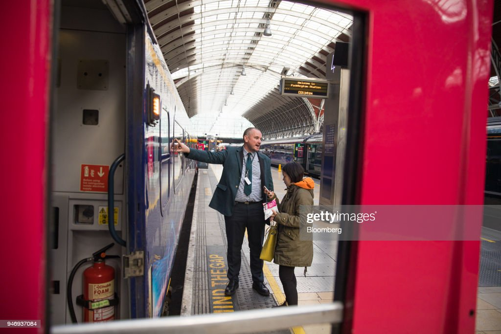 A member of Great Western Railway staff assists a passenger at London Paddington railway station in London, U.K., on Monday, April 16, 2018. British train and bus operator FirstGroup Plc, which operates the Great Western Railway,  said it rejected an 'opportunistic' takeover proposal that private-equity firm Apollo Management made as the company struggles with under-performing rail routes in the U.K. and competition from discount airlines in the U.S. Photographer: Jason Alden/Bloomberg via Getty Images