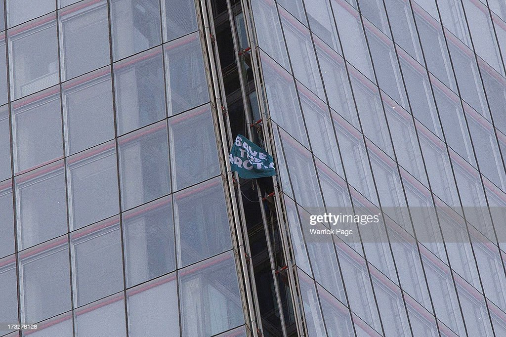 A member of Greenpeace displays a flag to a news media helicopter while scaling the Shard, the tallest building in western Europe, on July 11, 2013, in London, England. The six female protesters began their unauthorised ascent of the 310 metre high skyscraper shortly after 4am with the intention of highlighting the environmental damage caused by drilling for oil in the Arctic by Shell.