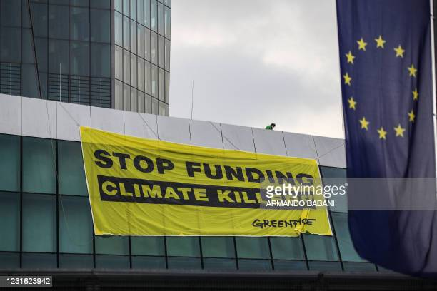 """Member of Greenpeace fixes a banner reading """"Stop funding climate killers!"""" on the roof of the European Central Bank in Frankfurt am Main, western..."""