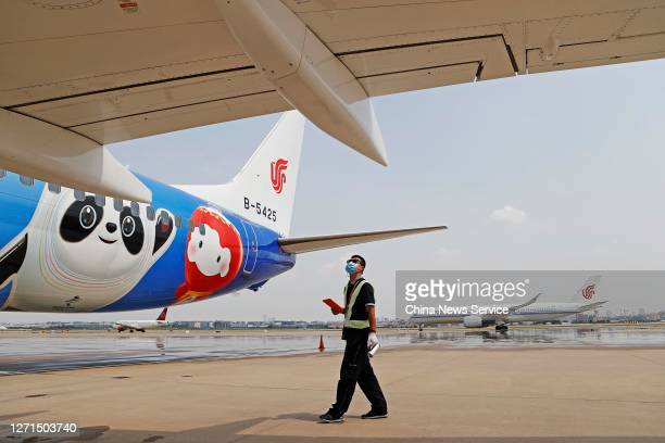 A member of ground crew inspects a newly painted Boeing 737 aircraft of Air China with patterns of the emblems and mascots of Beijing 2022 Winter...
