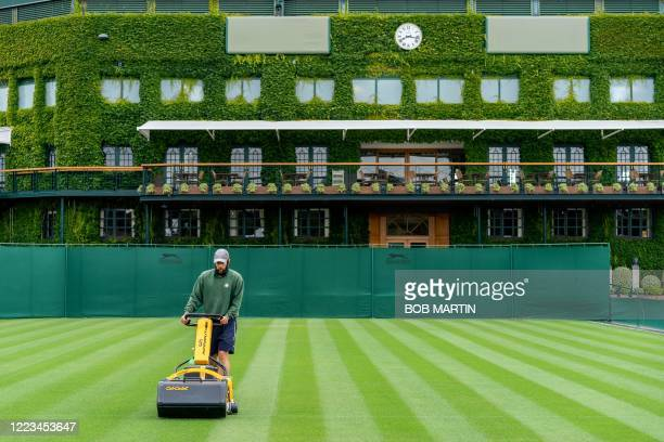 A member of ground staff tends to the grass on Court 6 to maintain the Wimbledon standards at the All England Lawn Tennis Club in west London on June...