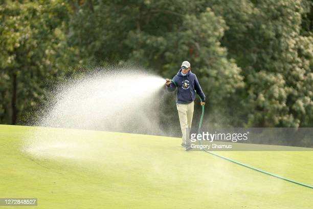 Member of grounds crew member waters the course during a practice round prior to the 120th U.S. Open Championship on September 16, 2020 at Winged...