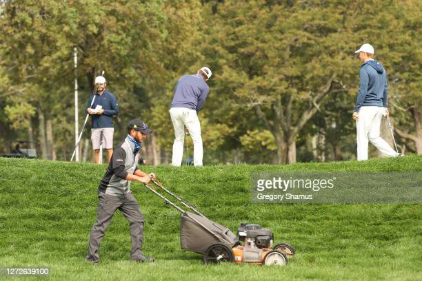 Member of grounds crew tends to the rough as golfers play a green during a practice round prior to the 120th U.S. Open Championship on September 15,...