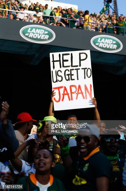 Member of Gwijo Squad, a sports fans movement, holds a placard as others sing in support of the South African Rugby National Team during the 2019...
