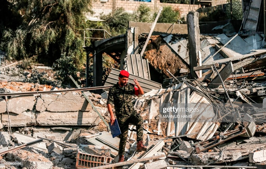 A member of Hamas' military police walks through rubble at a site that was hit by Israeli air strikes in Gaza City on August 9, 2018.