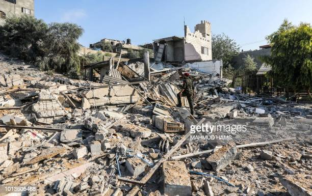 TOPSHOT A member of Hamas' military police walks through rubble at a site that was hit by Israeli air strikes in Gaza City on August 9 2018
