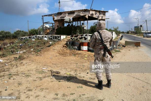 Member of Hamas movement's security apparatus inspects the site targeted by Israeli tank fire on the outskirts of Gaza City, near the border with...