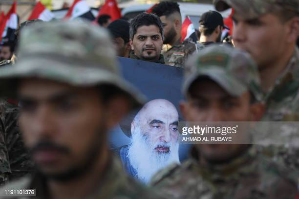 Member of Hashed al-Shaabi holds a picture of Iraq's top Shiite cleric Grand Ayatollah Ali Sistani during the funeral procession of fellow comrades...