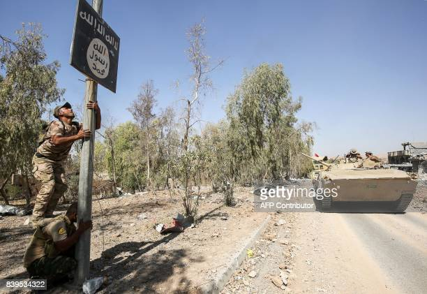 A member of Hashed AlShaabi removes a sign on a lamp post bearing the logo of the Islamic State group as Iraqi forces advance inside the town of Tal...