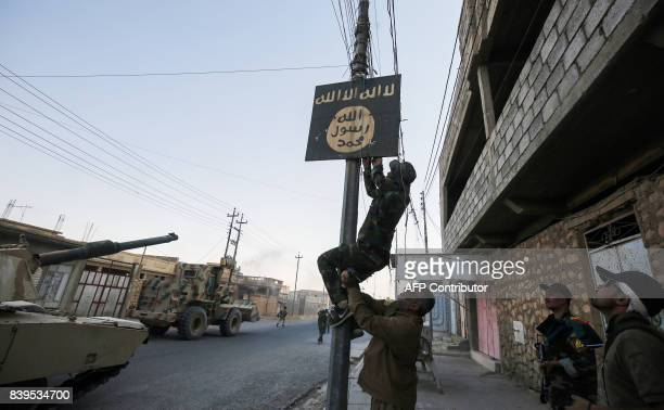 TOPSHOT A member of Hashed AlShaabi removes a sign on a lamp post bearing the logo of the Islamic State group as Iraqi forces advance inside the town...
