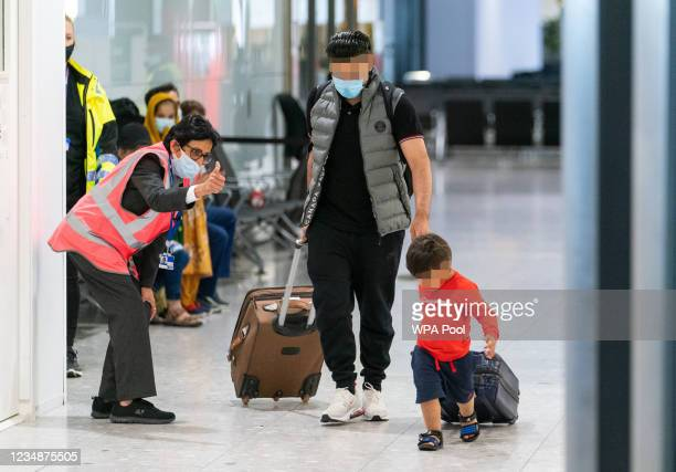 Member of Heathrow security staff gives a thumbs up to refugees arriving from Afghanistan at Heathrow Airport on August 26, 2021 in London, England....