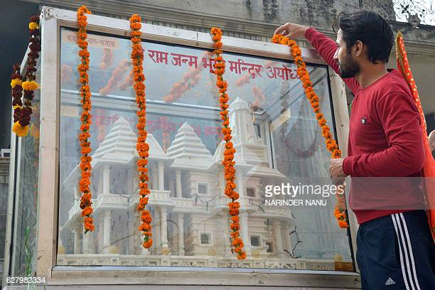 A member of Hindu Bajrang Dal garlands a model of a Ram temple during a procession marking the 24th anniversary of the demolition of the Babri Masjid...