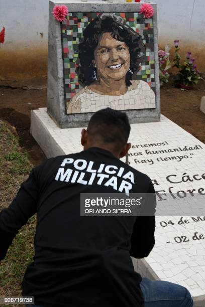 A member of Hondura's national military police in charge of the security of indigenous environmentalist Berta Caceres relatives cleans her grave in...