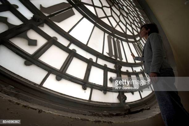 A member of House of Commons staff poses for a photograph in front of one of the deteriorating faces of the Great Clock ahead of the planned...