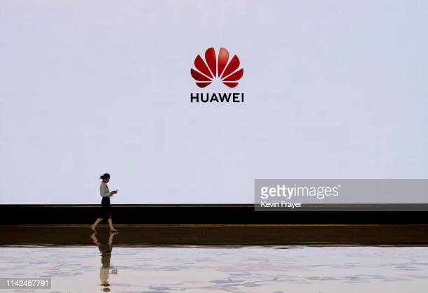 A member of Huawei's reception staff walks in front of a large screen displaying the logo in the foyer of a building used for high profile customer...