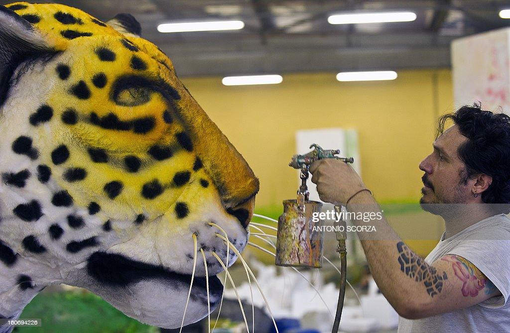 A member of Imperatriz Leopoldinense samba school paints a yaguarete effigy during preparations for the famous carnival parade at the Sambodromo, on February 4, 2013 in Rio de Janeiro. The samba schools parade will be held next February 10 and 11.
