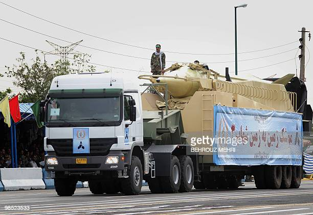 A member of Iran's Revolutionary Guards stands next to a longrange Shahab3 ballistic missile on a launcher truck during the Army Day parade in Tehran...