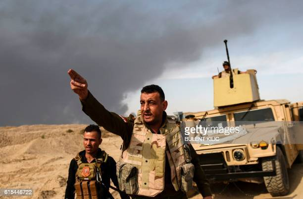 TOPSHOT A member of Iraqi forces gestures as troops head to the frontline on October 18 2016 near the town of Qayyarah south of Mosul during the...