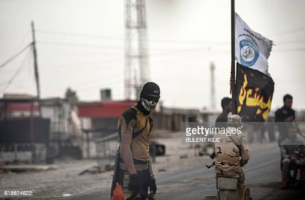 A member of Iraqi forces wearing a skull mask waits at a checkpoint for people fleeing the main hub city of Mosul on October 28 2016 between Qayyarah...