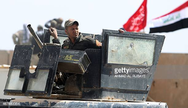 A member of Iraqi government forces stands on an armoured vehicle on the western outskirts of Tikrit on March 28 during a military operation to...