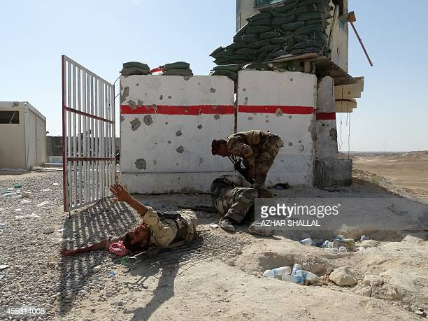 A member of Iraqi security forces backed by Sunni tribesmen gives assistance to comrades who were wounded during an attack at a military post during...