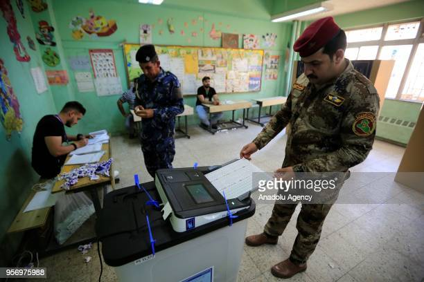 A member of Iraqi security forces puts his ballot paper in an electronic box following casting his vote during the special voting day for the Iraqi...