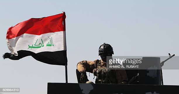 A member of Iraqi security forces sits on an armoured vehicle mounted with a national flag on February 12 after security forces retook the eastern...