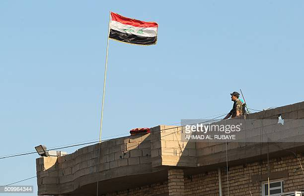 A member of Iraqi security forces stands on a roof on February 12 after security forces retook the eastern outskirts of Ramadi city from Islamic...