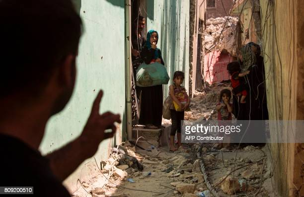 A member of Iraq's CounterTerrorism Service gestures towards an Iraqi family that emerged from a damaged building Old City of Mosul on July 5 as they...