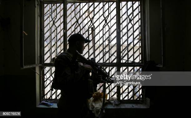Member of Iraq's Counter-Terrorism Service looks through a window while advancing in a building in the Old City of Mosul on July 5 during the...