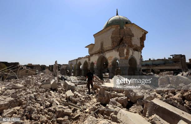 A member of Iraq's CounterTerrorism Service walks past part of the destroyed AlNuri Mosque in Mosul's old city on July 30 2017 With Mosul in ruins...