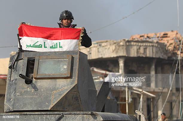 A member of Iraq's elite counterterrorism service raises his national flag on December 28 2015 after Iraqi forces recaptured Ramadi the capital of...