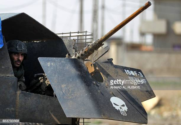 A member of Iraq's elite CounterTerrorism Service sits in an armed vehicle as they advance towards Mosul's alNasser neighbourhood on March 14 2017...