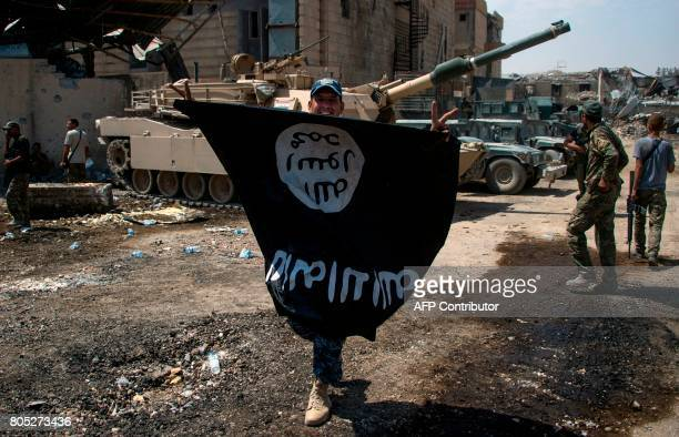 A member of Iraq's elite Rapid Response Division holds upsidedown the black flag of the Islamic State group as he patrols the Shifa neighbourhood on...