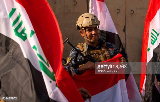 A member of Iraq's federal police holds Iraq's national flag as he celebrates with fellow members in the Old City of Mosul on July 9 2017 after the...