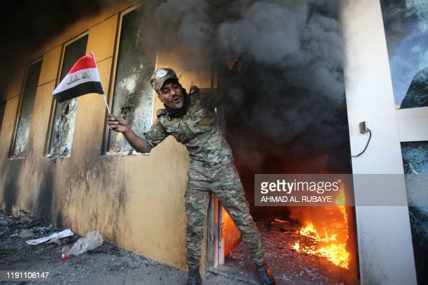 Member of Iraq's Hashed al-Shaabi military network waves a national flag as he exits a burning room after breaching the outer wall of the US...