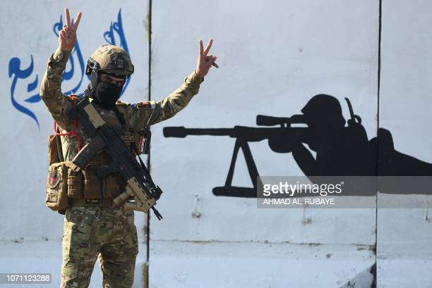 A member of Iraq's Rapid Response military flashes the Vsign for victory during celebrations at a military base inside Baghdad's International...