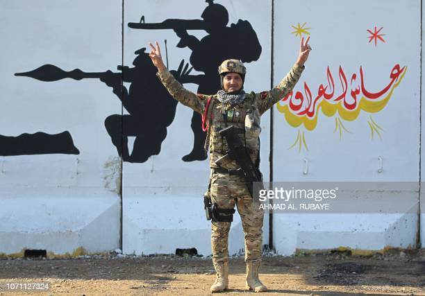 A member of Iraq's Rapid Response military unit poses for a picture in front of a mural golrifying the Iraqi forces during a ceremony at a military...