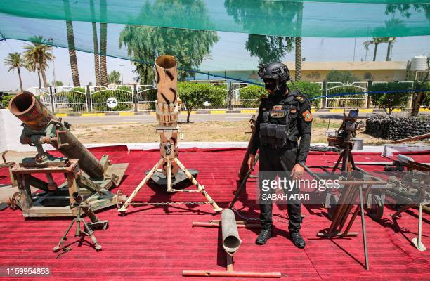 Member of Iraq's Special Operations Forces stands by artillery weapons seized by Iraqi security forces from areas formerly held by Islamic State...
