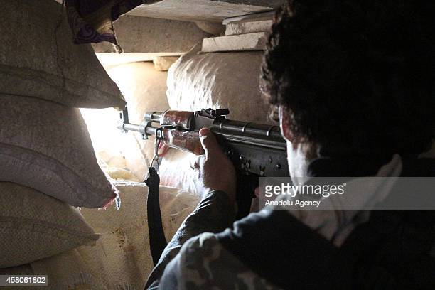 A member of Islamic Front a coalition of several rebel groups fighting in Syria aims his weapon through a hole in the wall towards Syrian regime...