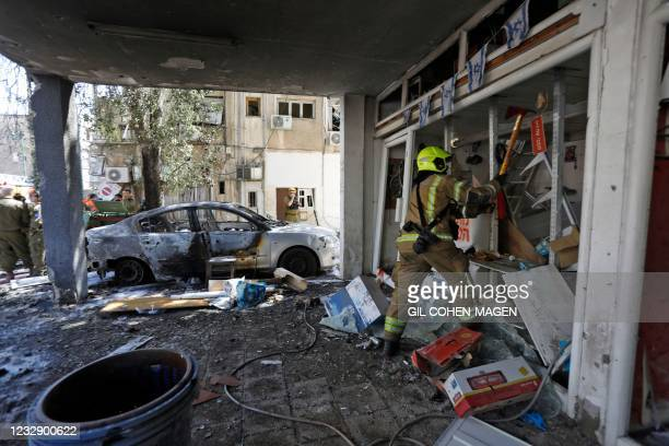 Member of Israeli emergency services works on a site hit by a rocket in Ramat Gan near the coastal city of Tel Aviv, on May 15 following the...