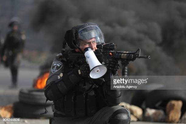 A member of Israeli security forces aims with his weapon as he holds a megaphone while they intervene in a protest against US decision to recognize...